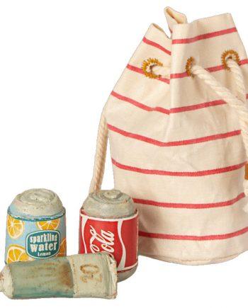 vit och röd randig strandväska med två burkar läsk och en tub solkräm i miniatyr