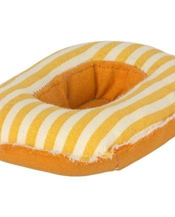 Gummibåt av gul randig textil. Denna lilla båt är en leksak.