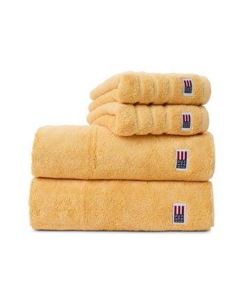 Handdukar av frotté i riktigt god kvalitét från Lexington. Handduken med färgen sunny yellow är en ljusgul handduk. Handduken har jacquardränder och en Lexingtonflagga nedtill samt en ögla för upphängning.