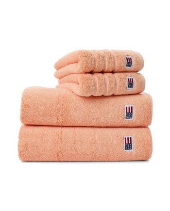 Handdukar av frotté i riktigt god kvalitét från Lexington. Handduken med färgen apricot är en aprikosfärgad handduk. Handduken har jacquardränder och en Lexingtonflagga nedtill samt en ögla för upphängning.